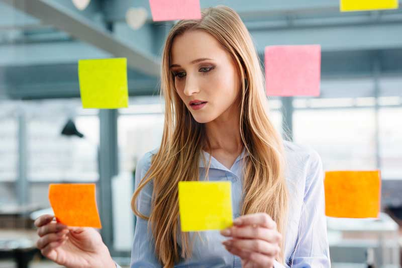 woman looking at sticky notes